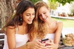 2 девочка-подростка используя мобильный телефон сидя на скамейке в парке Стоковое Изображение