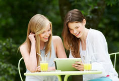2 девочка-подростка используя таблетку цифров в внешнем кафе Стоковая Фотография