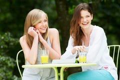 2 девочка-подростка используя таблетку цифров в внешнем кафе Стоковые Изображения