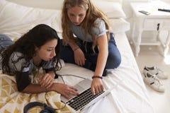 2 девочка-подростка на кровати используя компьтер-книжку, повышенный конец взгляда вверх Стоковое фото RF