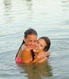 2 девочка-подростка обнимая в реке Стоковое Изображение