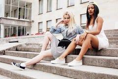 2 девочка-подростка перед зданием университета усмехаясь, имеющ потеху, концепцию людей образа жизни Стоковая Фотография RF
