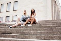 2 девочка-подростка перед зданием университета усмехаясь, имеющ потеху, концепцию людей образа жизни Стоковая Фотография