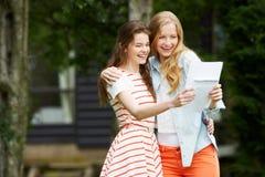 2 девочка-подростка празднуя успешные результаты экзамена Стоковые Фотографии RF
