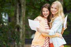 2 девочка-подростка празднуя успешные результаты экзамена Стоковая Фотография
