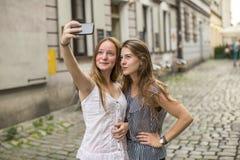 2 девочка-подростка принимают selfie на smartphone на улице района города старого Стоковая Фотография