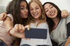 3 девочка-подростка принимая selfie дома, фокус на девушках Стоковое фото RF