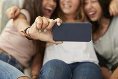 3 девочка-подростка принимая selfie дома, фокус на телефоне Стоковые Изображения