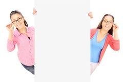 2 девочка-подростка при стекла стоя за пустой панелью Стоковые Изображения RF
