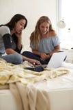 2 девочка-подростка сидя на кровати используя компьтер-книжку, вертикальную Стоковое фото RF