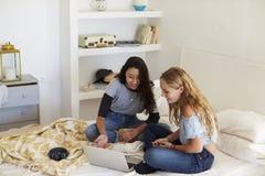 2 девочка-подростка сидя на кровати используя портативный компьютер Стоковое фото RF
