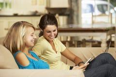 2 девочка-подростка сидя на софе дома используя планшет и компьтер-книжку Стоковые Изображения