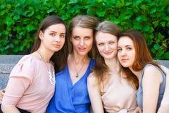 4 девочка-подростка сидя на стенде в парке лета Стоковое Изображение RF