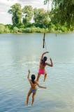 2 девочка-подростка скача в реку Стоковые Изображения