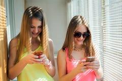 2 девочка-подростка смотря в их устройствах Стоковые Изображения RF