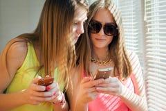 2 девочка-подростка смотря в их устройствах Стоковые Фото