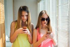 2 девочка-подростка смотря в их устройствах Стоковые Фотографии RF