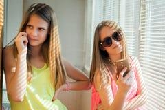 2 девочка-подростка смотря в их устройствах Стоковое Изображение RF