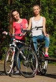 2 девочка-подростка с велосипедом в парке Стоковая Фотография