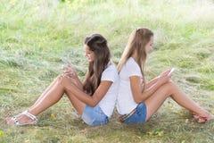 2 девочка-подростка с сотовыми телефонами сидят на траве Стоковое Фото