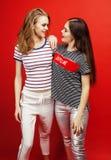 2 девочка-подростка лучших другов совместно имея потеху, представлять эмоциональный на красной предпосылке, усмехаться besties сч Стоковая Фотография
