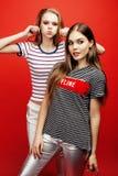 2 девочка-подростка лучших другов совместно имея потеху, представлять эмоциональный на красной предпосылке, усмехаться besties сч Стоковое Фото