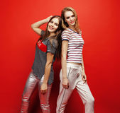 2 девочка-подростка лучших другов совместно имея потеху, представлять эмоциональный на красной предпосылке, усмехаться besties сч Стоковое Изображение RF