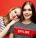 2 девочка-подростка лучших другов совместно имея потеху, представлять эмоциональный на красной предпосылке, усмехаться besties сч Стоковые Изображения RF