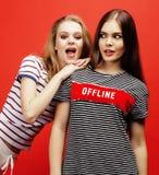 2 девочка-подростка лучших другов совместно имея потеху, представлять эмоциональный на красной предпосылке, усмехаться besties сч Стоковые Фотографии RF
