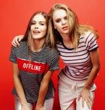 2 девочка-подростка лучших другов совместно имея потеху, представлять эмоциональный на красной предпосылке, усмехаться besties сч Стоковая Фотография RF