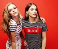 2 девочка-подростка лучших другов совместно имея потеху, представлять эмоциональный на красной предпосылке, усмехаться besties сч Стоковые Фото