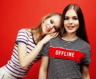 2 девочка-подростка лучших другов совместно имея потеху, представлять эмоциональный на красной предпосылке, усмехаться besties сч Стоковое фото RF
