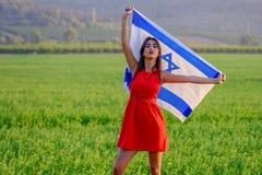 Еврейская девушка с флагом Израиля на изумляя ландшафте красивым летом стоковые фото
