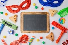 Еврейская концепция Purim праздника с hamantaschen печенья, маска масленицы и доска на белой предпосылке Стоковые Изображения RF