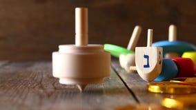 Еврейский отснятый видеоматериал Хануки праздника с верхней частью традиционного деревянного dreidel spinnig закручивая видеоматериал