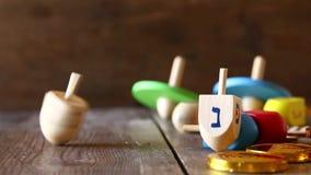 Еврейский отснятый видеоматериал Хануки праздника с верхней частью традиционного деревянного dreidel spinnig закручивая акции видеоматериалы
