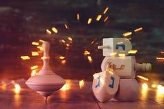 еврейский праздник Ханука с деревянным собранием dreidels & x28; закручивая top& x29; и света гирлянды золота на таблице стоковое фото rf
