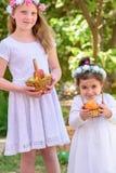 Еврейский праздник Shavuot Маленькие девочки HarvestTwo в белом платье держат корзину со свежими фруктами в саде лета стоковое изображение rf