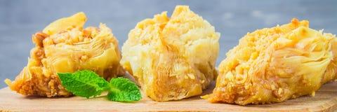 Еврейский, турецкий, арабский традиционный национальный десерт Макрос Селективный фокус Бахлава с медом и гайками, знаменем Стоковые Изображения RF