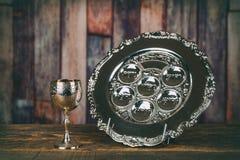 Еврейский matzah Pesach еврейской пасхи праздников и серебряная чашка полная вина с традиционным благословением стоковое изображение