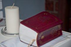 Еврейское традиционное положение книги на таблице около большой белой свечи Стоковое Изображение RF