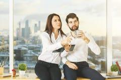 Европейские бизнесмен и женщина на windowsill Стоковое Изображение