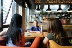 Европейские женщины сидя на уютном кофе кафа, усмехаться и выпивать Стоковые Изображения