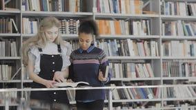 Европейские и Афро-американские женщины книга чтения в библиотеке акции видеоматериалы