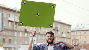 Европейские люди на ралли Кавказский человек с знаменем кричащим в мундштук