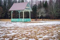 Европейский бизон и шкаф игры леса пустой питаясь с крышей металла в Bialowieza, Польше, отчасти снеге, зеленом hayrack, пасмурно стоковые фотографии rf