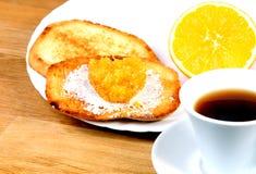 Европейский завтрак: чашка кофе, здравицы с вареньем и апельсин Стоковое Изображение RF