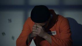 Европейский заключенный в тюрьму мужчина держа серебряный крест и моля в чувстве клетки виновном видеоматериал
