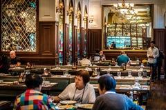 Европейский интерьер бистро с сервировками стола и цветным стеклом люстр Стоковые Фото