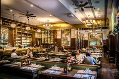 Европейский интерьер бистро с сервировками стола и цветным стеклом люстр Стоковое Фото